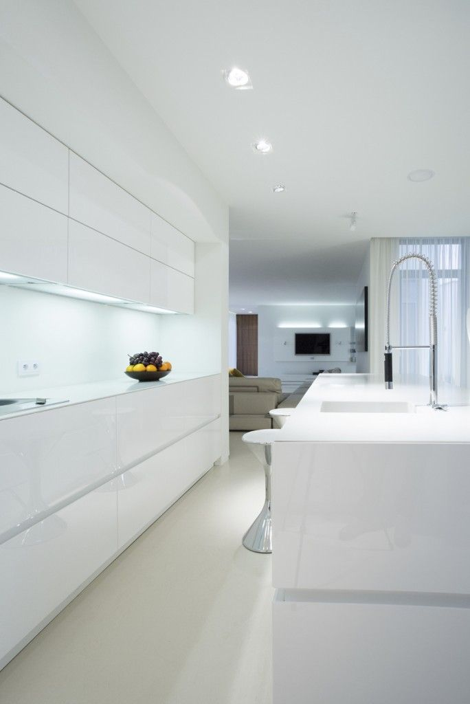 An all-white modern kitchen with a centered