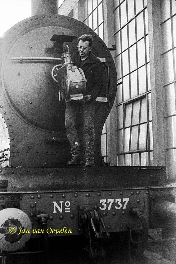 Een monteur verwijdert hier de lampen van de locomotief. Dat gebeurt bij de locomotiefhal bij de hoofdwerkplaats van de spoorwegen in Tilburg. Nu  Spoorzone genoemd.