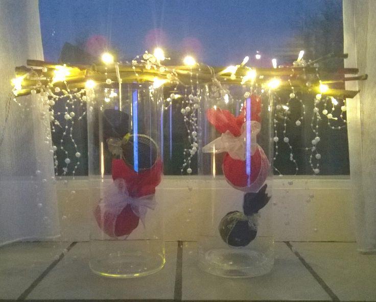 Takken met lichtjes horizontaal op twee hoge vazen met hangende kerstballen erin.