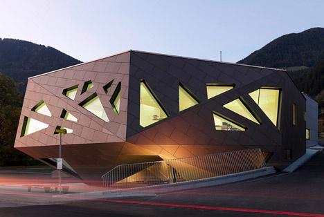 Centro Comunitário em Abfaltersbach, Tirol (Áustria),consiste em três partes principais (auditório,sala de ensaios de música,a Câmara Municipal) e o Corpo de Bombeiros.Projeto da empresa austríaca Machné    Architekten, o edifício é  feito de   madeira efibra-cimento revestindo os volumes que são dobrados para enquadrar pontos de vista dos prédios ao redor.Um hall de entrada envidraçado conecta os três blocos principais em seu centro e oferece entradas aos departamentos.