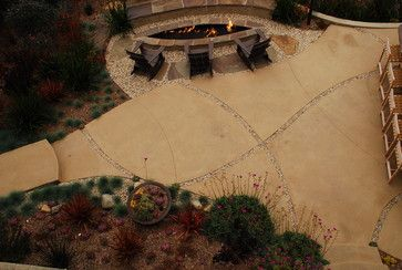 Colored concrete with decorative rock channels for water infiltration. Love the shape of the fire pit, too!