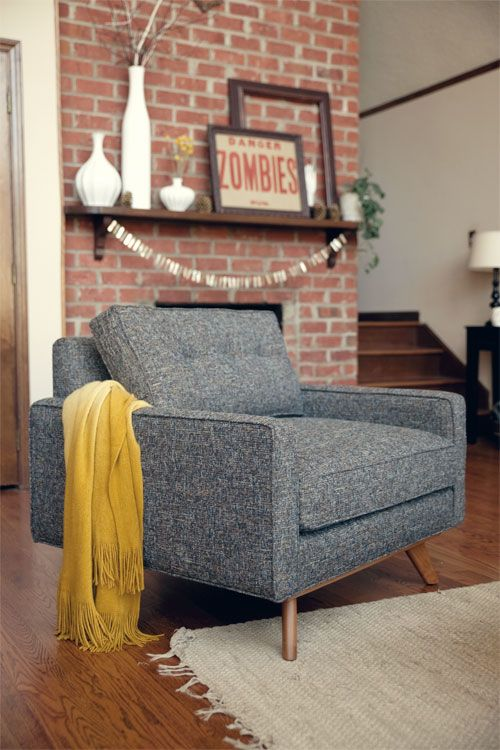 chair love. This is pretty much my style to a T. I love the brick wall, the chair, the floor, the throw, the rug, the vases, and especially that framed zombies sign and empty frame. Just a small frame of the space and it feels nice and open. love.