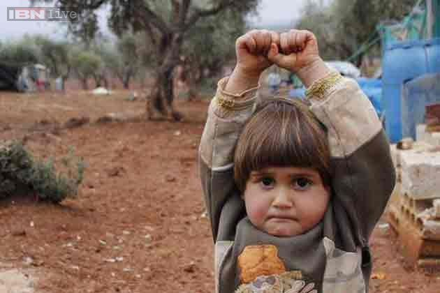 In a breathtaking instance, photojournalist Nadia AbuShaban tweeted a photo of a child in Syria holding her hands up in surrender.