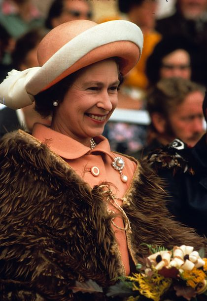 Wearing a ceremonial cape made of bird feathers in New Zealand, the Queen sports a creamsicle orange suit and hat with cream trim on the band.