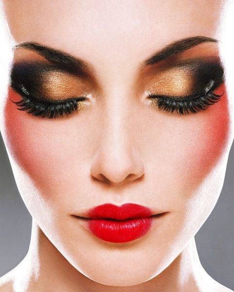 Dramatic gold and black eye makeup with red lips