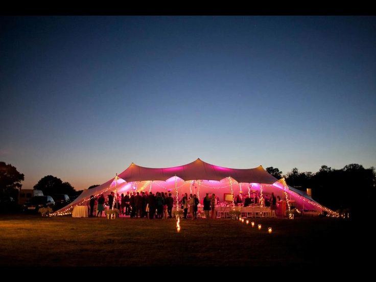 As the sun goes down, the party is starting. 20m x 25m in ivory showing how fantastic lighting creates your style. Photography by Caught the Light Contact freestretch.co.uk for similar #marquee #stretchtent #weddingvenue and #lights.