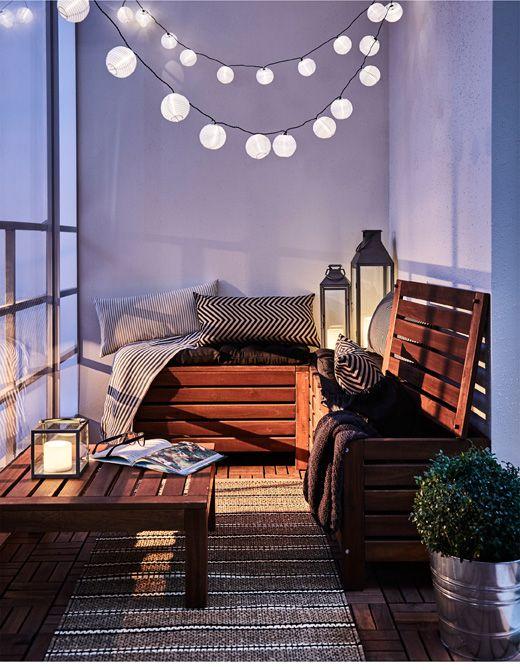 Rincón de descanso acogedor en un balcón, con artículos textiles y una guirnalda de luces.