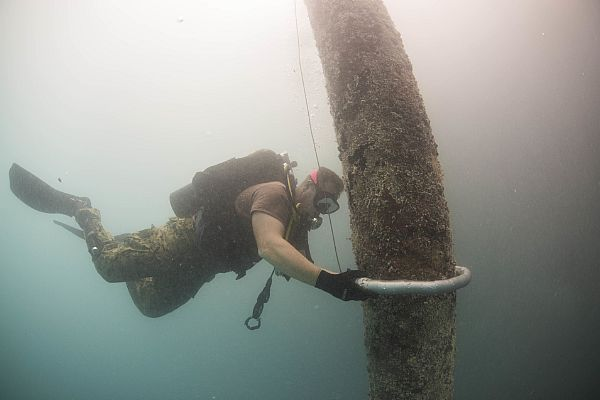 Petty Officer 1st Class David Miller, Underwater Construction Team (UCT) 2, assigned to Commander, Task Force (CTF) 75, places a shaped charge to a damaged pylon in Diego Garcia.