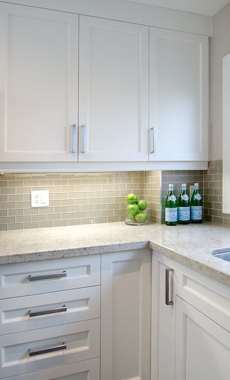 L shaped kitchen features white cabinets paired with speckled countertops and gray glass mini-subway tile backsplash.