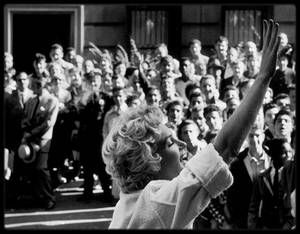 """1954 / Marilyn saluant la foule et les fans sur les marches du bromstowne typique de New York où elle tourne, situé au 164 East, 61 st Street ; """"Sept ans de réflexion"""", sorti durant l'été 1955, est le plus grand succès de l'année pour la """"20th Century Fox"""". Mais la route fut longue et parsemée d'embûches. Le film est l'adaptation d'une pièce à succès qui a tenu le haut de l'affiche à Broadway pendant trois ans. George AXELROD écrit volontiers avec WILDER l'adaptation de sa pièce de théâtre…"""