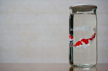 透明のガラス瓶に、朱色の鯉が泳いでるように見える。全国日本酒カップコンクールでデザイン賞をもらっています。こめどころ新潟の小千…