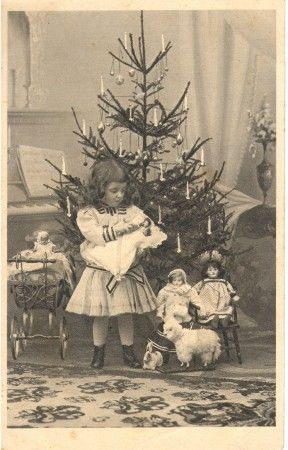 A little girl and her dolls & toys celebrate Christmas..