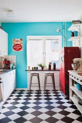 Esta cozinha deu um ar moderno ao vintage, com a parede em turquesa e as banquetas de design industrial. Destaque para a geladeira em vermelho.