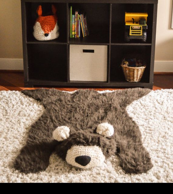 Add rustic charm to any room with this adorable handmade faux bear rug! This bears body is crafted out brown faux grizzly fur and measures 50 inches long x 32 inches wide. The bears muzzle and ears are crocheted with a cream-colored yarn with a black felt nose. This precious rug is wonderful for baby showers, birthdays, and other gifting occasions.  The bear rug is NOT attached to the cream colored rug in the listing photos. The cream colored rug is NOT included.  This unique bear rug is…