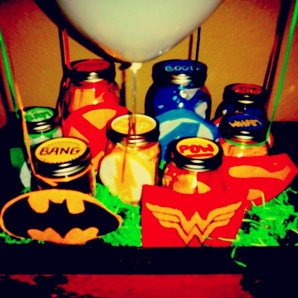 Superhero center piece made out of mason jars and streamers with balloons attached.