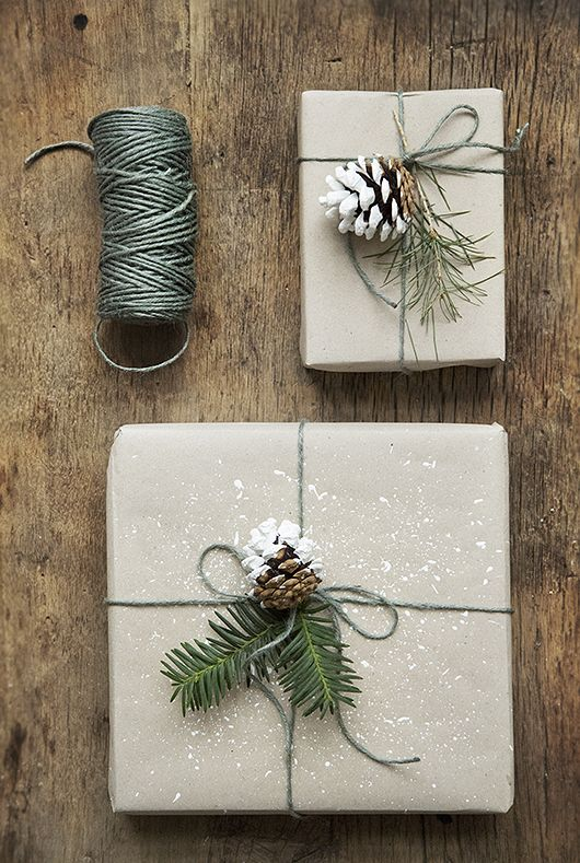 I love the splatter of white paint on the plain wrapping paper. Lovely creative gift wrapping using real evergreen pine boughs and pine cones.