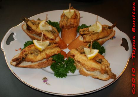 """Recipe: Tapas Anchovies Stuffed with Paprika Pintxos Anchoas Rellenas de Pimientos- This Basque pintxo recipe consists of a slice of crispy bread loaded with fried anchovies stuffed with roasted bell pepper. This style of tapas on bread is very common in the tapas bars and tapas restaurants of San Sebastian, Bilbao and other places in the Basque Country where in the Basque language they are called """"pintxo""""."""