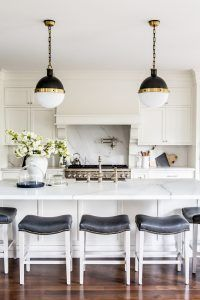 White Kitchen Island with Black Leather Saddle Counter Stools. White Kitchen Island with Black Leather Saddle Counter Stools. Gorgeous kitchen features white shaker cabinets paired with white marble countertops with gray veining and matching backsplash. A white French kitchen hood with corbels stands over a swing arm pot filler and a stainless steel stove. A pair of Hicks Pendants illuminate a long white kitchen island fitted with a farmhouse sink and deck mount vintage faucet lined with…
