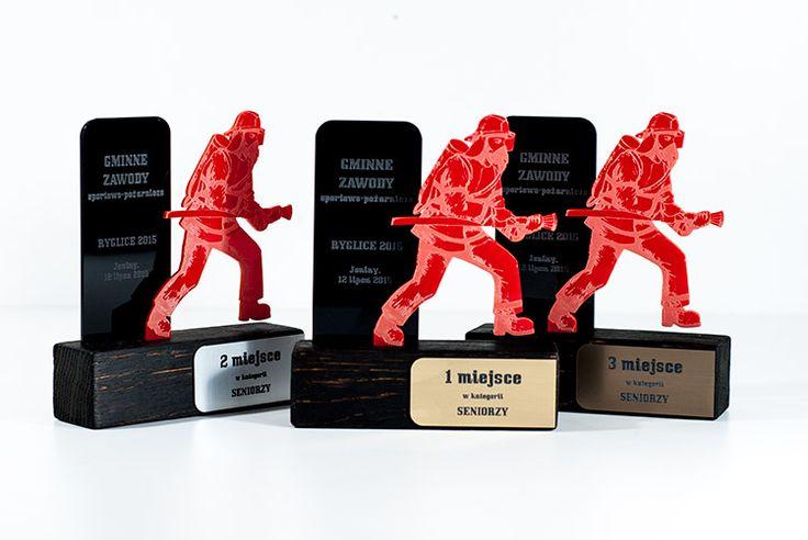 Oryginalne statuetki na gminne zawody sportowo-pożarnicze.Zostały wykonane z drewna, pleksi czarnej i czerwonej grawerowanej oraz laminatu grawerskiego.