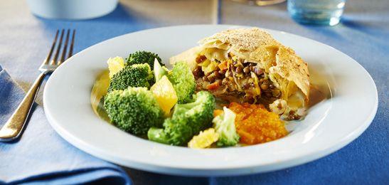 Knapperige rol met linzen, abrikozen en hazelnoten, wortel-gembersaus en broccoli.