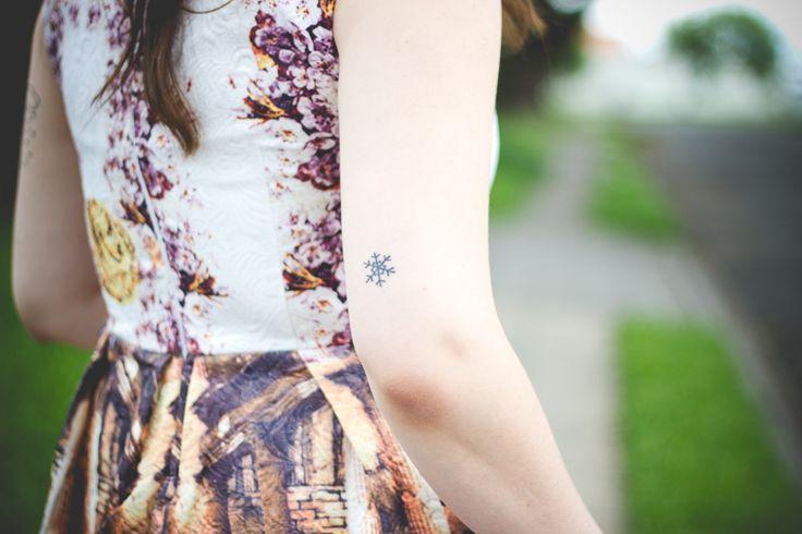 Tatuagem delicada de floquinho de neve na parte de trás do braço acima do cotovelo direito.
