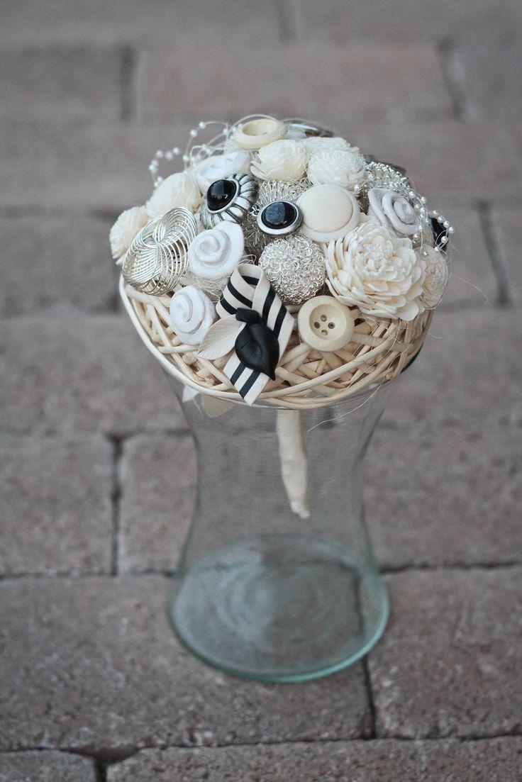 A csokor rattan alapra készült, ragasztott és drótozott technikával. A virág fejek sajátkészítésű kerámia virágok, vintage jellegű borossok,gombok, ékszerek, melyek gyöngyök, fémek, műanyagok. Fehér szatén szalag takarja körben a szárát!Mérete: kb 20 cm átmérőjű. Igazi modern fiatalos csokor!