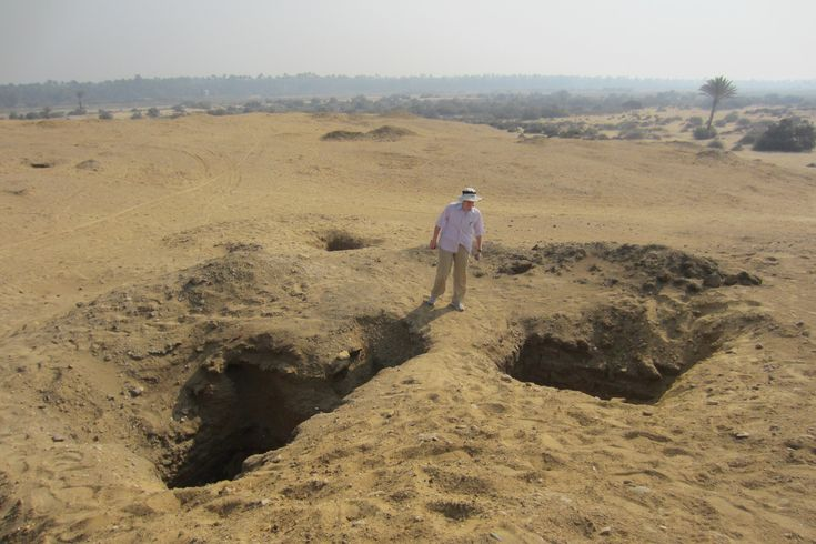 Sarah Parcak stands next to two massive looting holes on an Egyptian dig in December 2014. Before 2011, the tombs underneath were virtually unlooted.