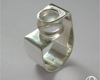 The crystal is held by the tension between the two tubes allowing it to move yet stay in place. The ring has a bright polished finish that can be customized in other finishes. Available also with Jade (see picture). As with all of my rings, this is handcrafted and unique. This ring will be made by order in your size, with the finish that you prefer and the same stone. Between 5 to 8 days are needed to make and send this ring to any part of the world. La esfera de cristal se sostiene por…