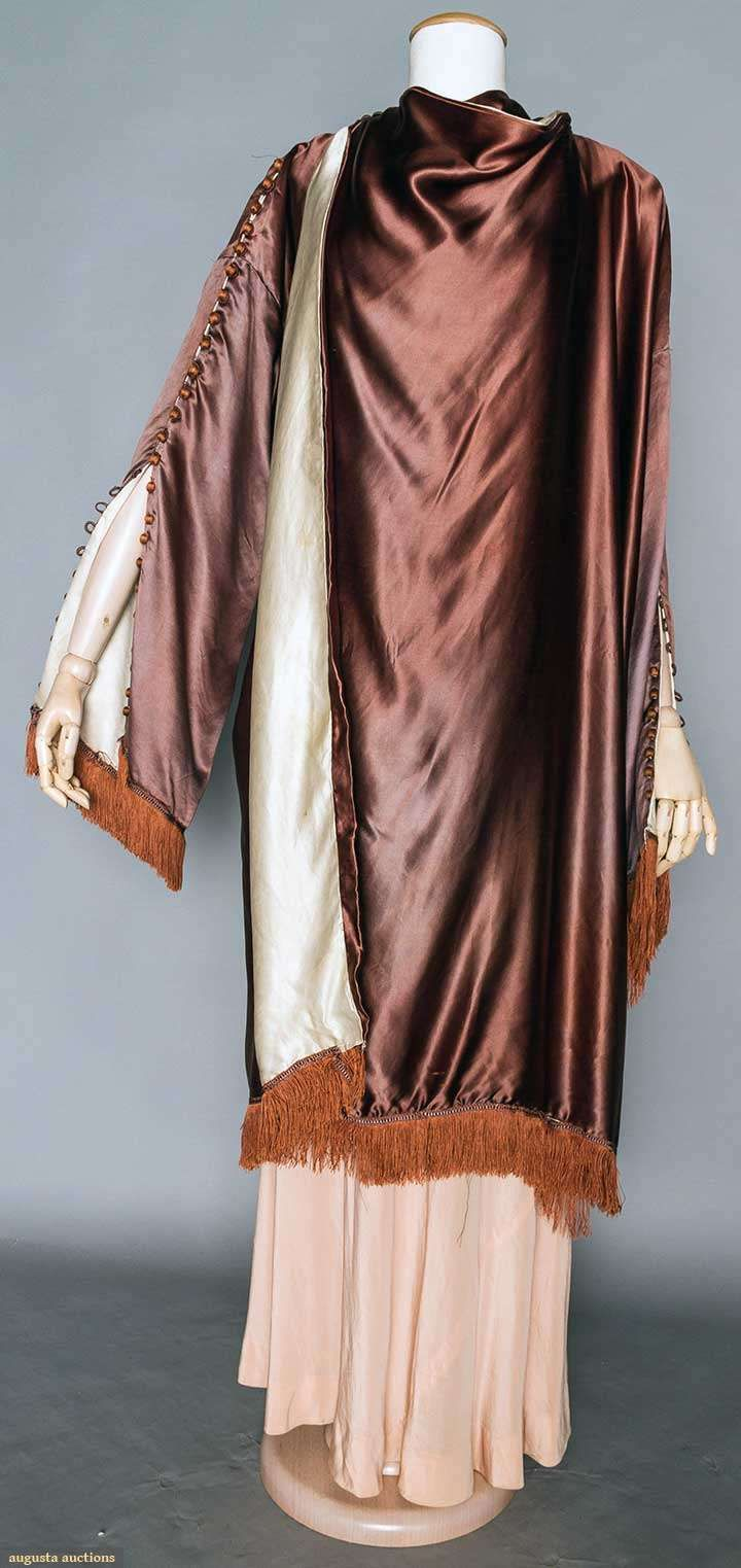 Poiret silk evening wrap, Paris, 1917 Unlabeled, the MET & FIT museums have same garment in different color. Eggplant silk charmeuse, white silk charmeuse lining, wide sleeves w/ rust thread ball buttons from shoulders to rust fringed sleeve hem, wide F panel wraps over right shoulder, 2 fringed tabs fall to back at shoulders