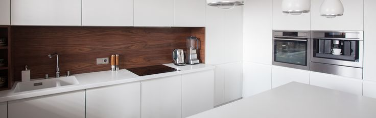 Nowoczesny, minimalistyczny design drewnianej kuchni, w której przeplata się biel szafek i ciemny brąz paneli ściennych i podłogowych. kitchen with white cupboards and dark brown wall and floor panels.