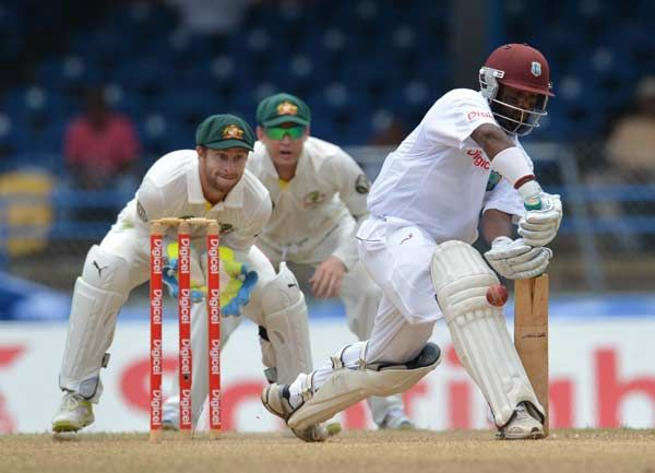 West Indies batsman Shivnarine Chanderpaul (R) plays a shot as Australian wicketkeeper Peter Nevill (L) and Michael Clarke (C) look on during the third day of the second-of-three Test matches between Australia and West Indies April 17, 2012 at Queen's Park Oval in Port of Spain, Trinidad.