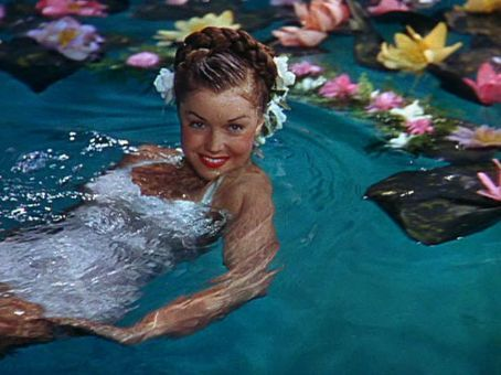 """In memoriam - Esther Williams (1921-2013) was a competitive swimmer who became one of the top box-office stars at MGM in the 40's & 50's in a series of spectacular technicolor """"aquamusicals"""", which featured lighthearted stories, musical numbers, and elaborate swimming peformances.  Created solely for her, this unique genre not only made millions, but helped popularize swimming as recreation and entertainment for an entire generation."""