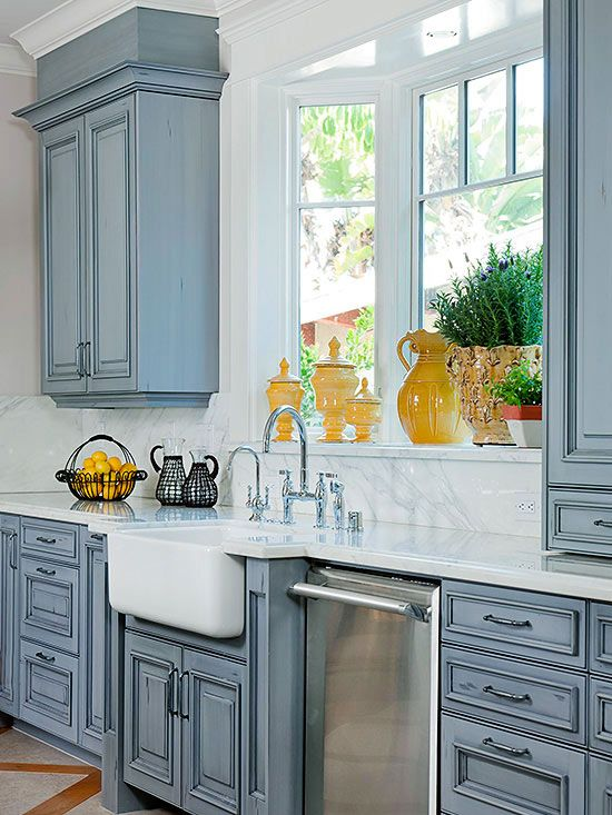 Painted Cabinets and Farmhouse Sink A beautiful blue glaze covers the new cabinets in this kitchen, playing perfectly off the graining in the marble countertops. The large white farmhouse sink sits below a trio of windows, allowing a perfect view to the outdoors.
