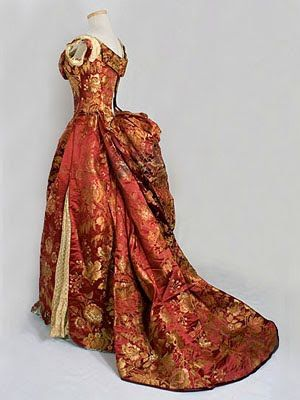 bustle evening dress- decorative fabrics, cut sleeves that were short and covered just the shoulders. Necklines varied by square, v shape, or round and low.