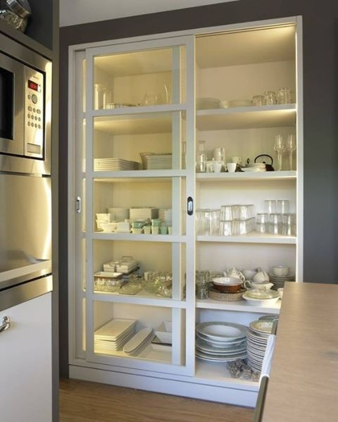 floor to ceiling, glass fronted and backlit pantry for glasses, plates, china storage. Great use of space