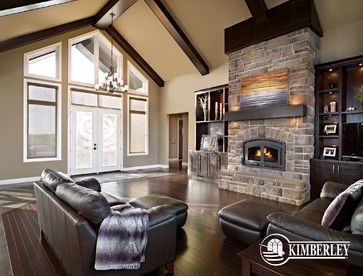 Stone fireplace and hearth, with built-ins flanking it. Accent lights in the mantle. Custom acreage bungalow by Kimberley Homes #interiordesign #newhomedesign #homedesign #newhome #customhome #yegre #buildwithkimberley #kimberleyhomes #fireplace #greatroom #livingroom #bonusroom #stonewall #accentwall #builtinbookcase #builtinshelves