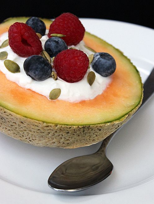 Breakfast Idea: Yogurt-Filled Cantaloupe Bowl with raspberries, blueberries, and pumpkin seeds.