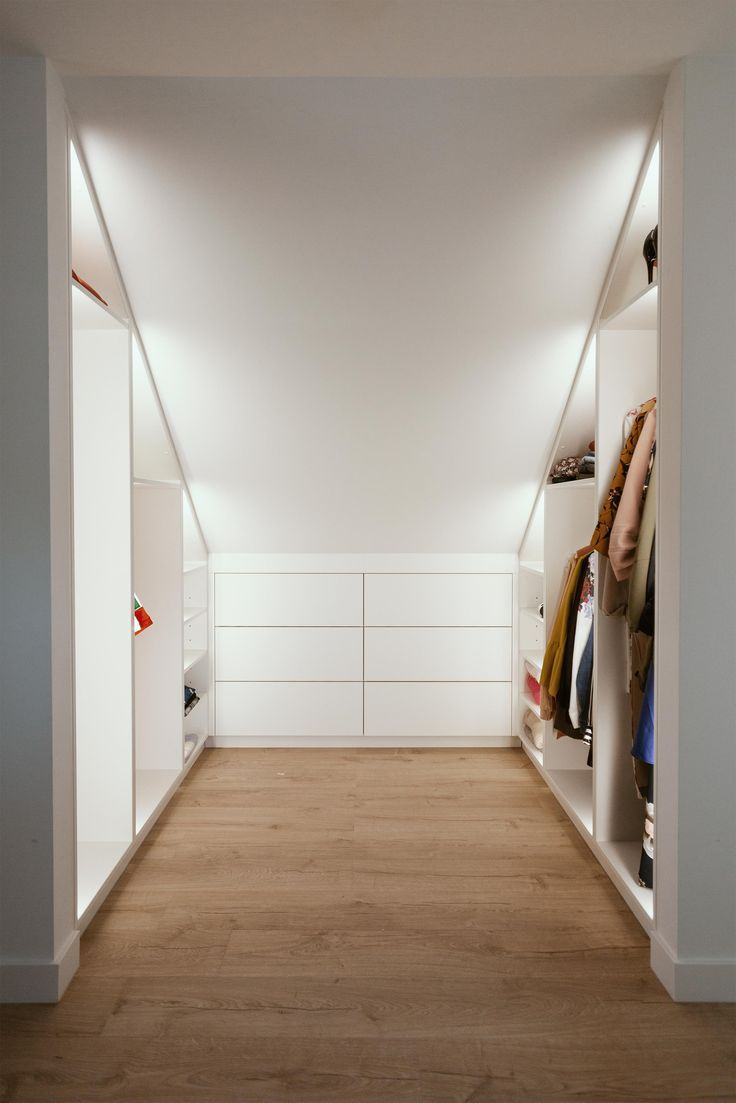 Walk-in closet under a sloping roof with indirect LED lighting.