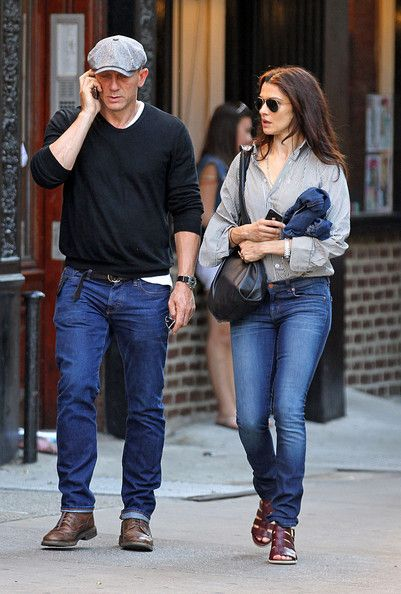 Daniel Craig casual look. Newspaper boy hat, black sweater, blue jeans & brown boots.