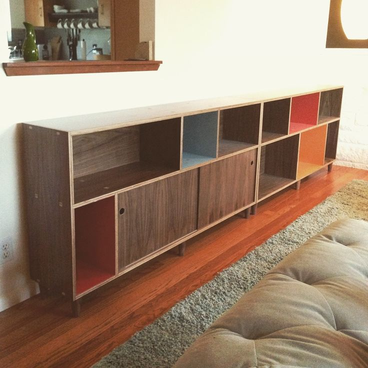 Walnut plywood bookcases with custom color laminate. Sliding doors and tons of fun, all set up in it's happy home. Made by Kerf Design in Seattle, Washington. kerfdesign.com