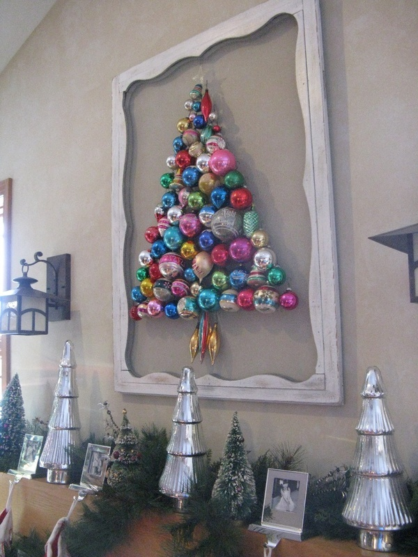 """The """"tree"""" is made by hooking ornaments thru the screen material on the back door in my kitchen.  I taped up some twine to get the shape and size I wanted and then just started adding the ornaments and filling in all the spaces"""