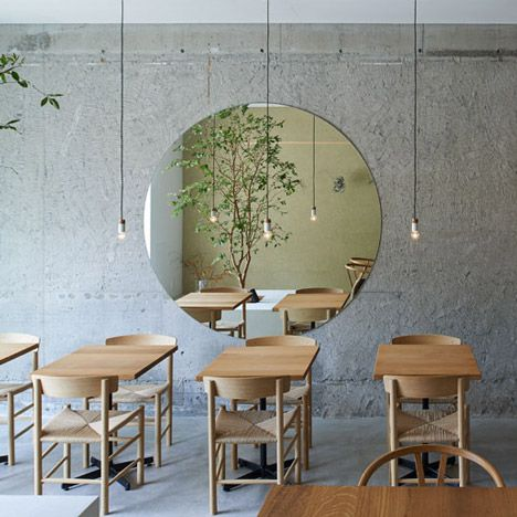 A large circular mirror reflects a tree planted in the centre of this Osaka cafe by Japanese studio Ninkipen!