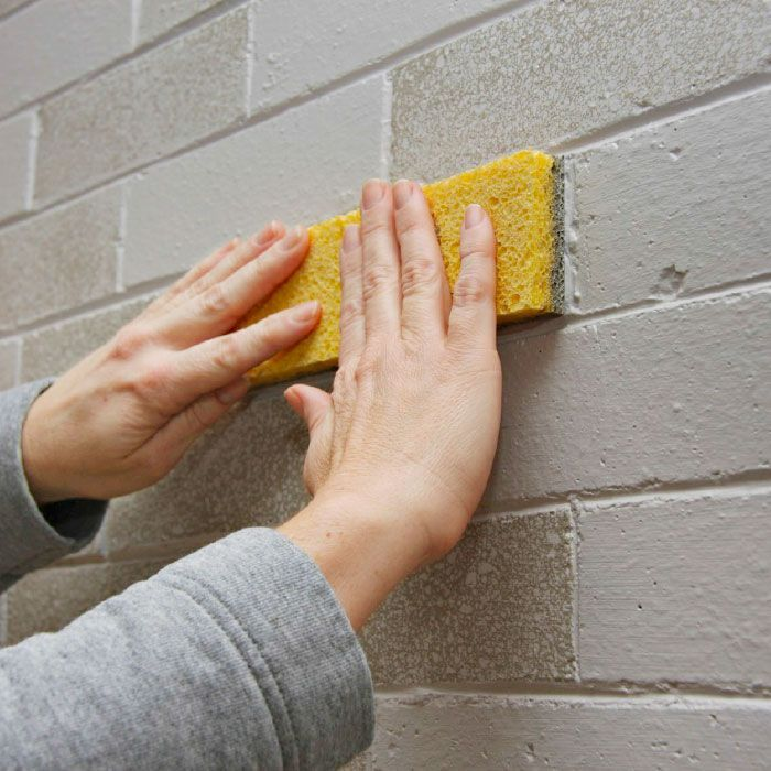 Sponging paint on a brick face.