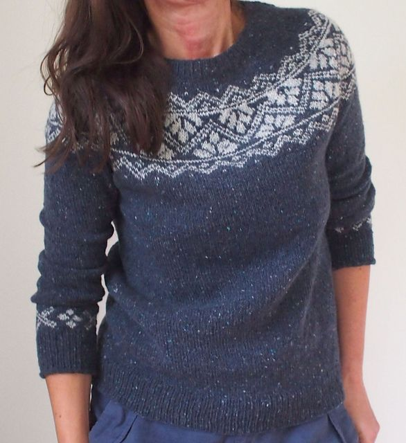 This circular-yoke sweater is worked seamlessly from the top down. After the neck ribbing is done, short rows are worked back and forth to shape the neckline. Then, the lovely, round, patterned yoke is worked in the round until sleeve separation. Sleeve stitches are placed on hold while the body is worked down to the hem. Then sleeve stitches are picked up again to knit the sleeves, with a small repeat of fair isle right before the final ribbing to echo the yoke pattern. All fair isle…