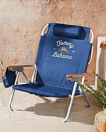 A Tommy Bahama exclusive! Embroidered with our orange-and-white design, this deluxe beach chair makes relaxing a breeze. With a lightweight, aluminum-and-steel frame, it's 2.5in. wider than other backpack chairs and collapses for hands-free toting. It reclines to 5 positions when unfolded and has hardwood armrests for a unique touch of quality. Insulated cooler pouch, cell phone holder, towel bar, adjustable pillow and more. Imported. TH31999.