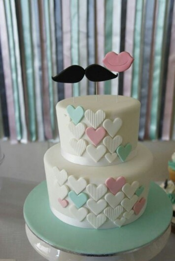 Seafoam and pink lips and moustache theme hearts engagement cake with a ribbon backdrop www.sweetcouture.com.au