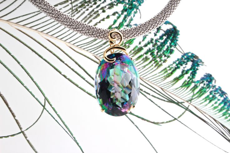 This pendant features a magnificent oval rainbow topaz set in 14k yellow gold.