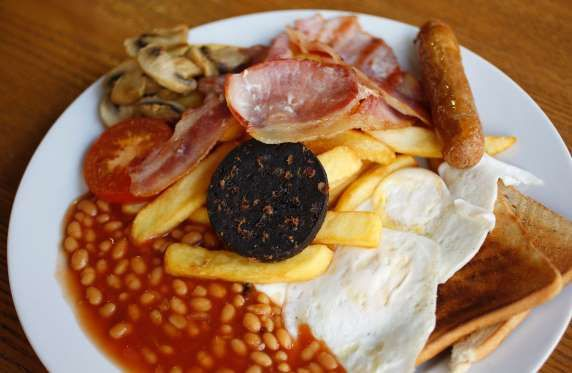 A traditional full English breakfast of sausages, chips, baked beans, bacon, black pudding and toast