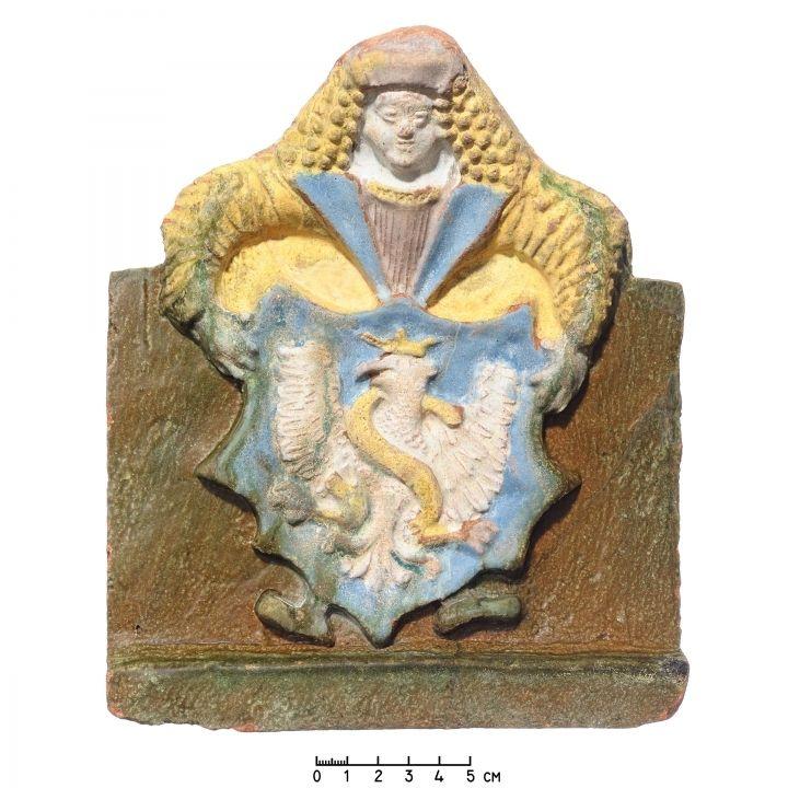 Karūninis koklis su skydininko laikomu Lenkijos herbu ir Žygimanto Senojo inicialu S (Sigismundus), XVI a. II ketv. Nacionalinis muziejus Lietuvos Didžiosios Kunigaikštystės valdovų rūmai, Vilnius. Šiuo metu eksponuojamas. Fotografas Vytautas Abramauskas. / Stove tile with a shield holder bearing the coat of arms of Poland (Eagle) and the letter S (the initial of Sigismund the Old), 2nd qtr. of the 16th c. National Museum Palace of the Grand Dukes of Lithuania, Vilnius. Currently on display.