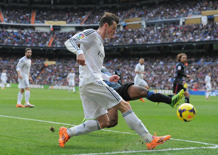 Gareth Bale crosses the ball while being tackled by Brayan Angulo of Granada CF during the La Liga match between Real Madrid CF and Granada CF at Santiago Bernabéu stadium on January 25, 2014 in Madrid, Spain.